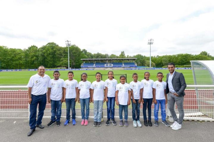 Ibrahim Ingare et Fabrice Abriel avec les enfants devant le terrain d'entraînement de l'équipe de France de football
