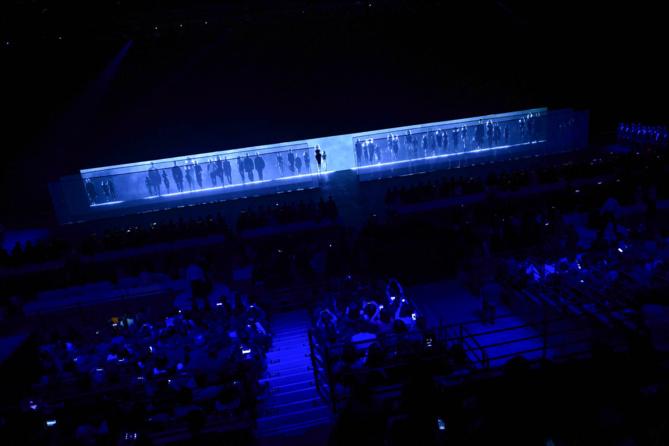 Dans un immense stade, un décor ultra épuré... Les mannequins vont défiler au coeur d'un labyrinthe de voile et de gauche à droite...