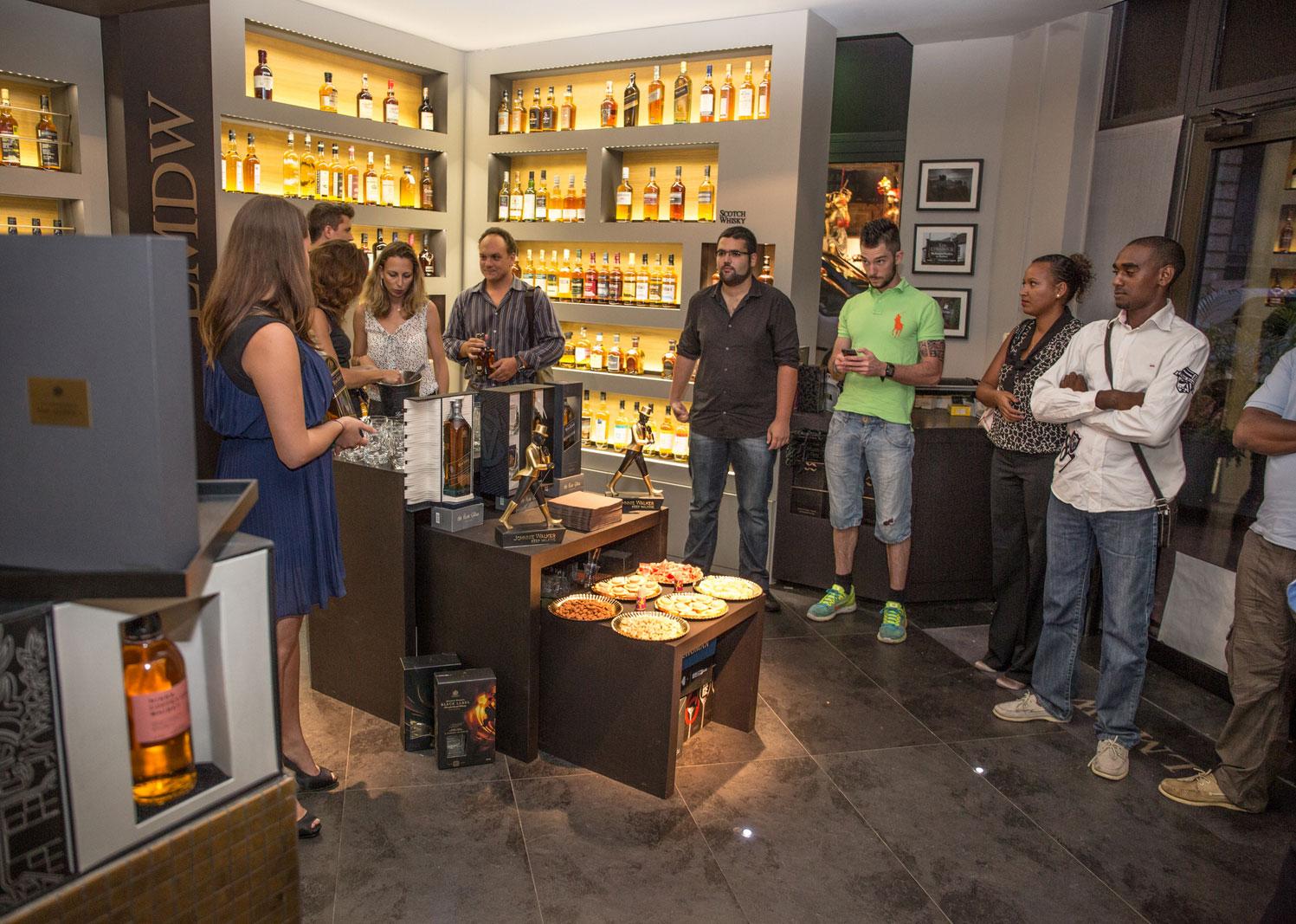 aStéphanie Jordan, la nouvelle Ambassadrice de la marque dans notre île, en pleine séance de dégustation Blue Label devant les privilégiés rassemblés à La Maison du Whisky
